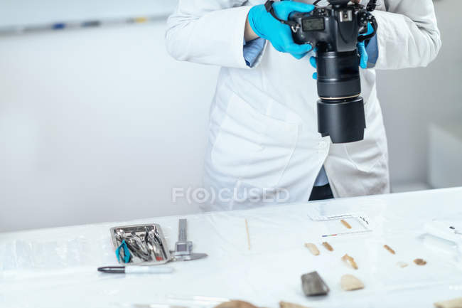 Female archaeology researcher documenting lithics with camera in laboratory. — Stock Photo