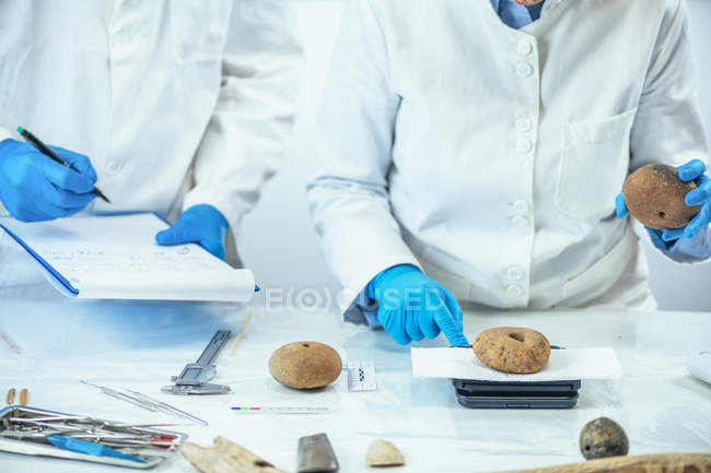 Two archaeologists measuring ancient artifacts in laboratory. — стокове фото