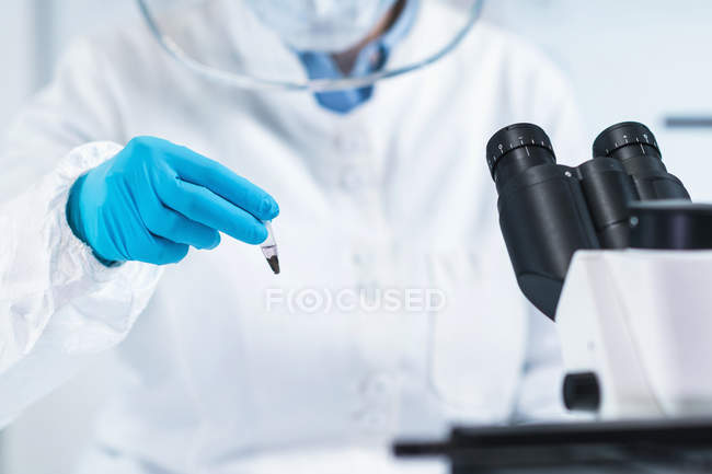 Female scientist holding micro tube with sample in ancient DNA laboratory for ancient DNA analysis. — Stock Photo