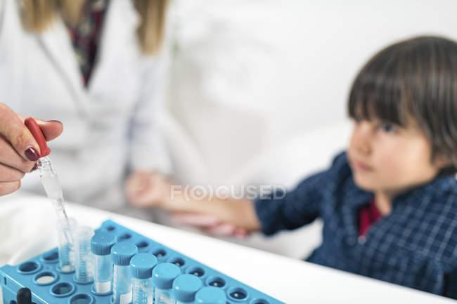 Ärztin führt Allergietest auf Hautstiche bei Jungen auf mögliches Allergen durch. — Stockfoto