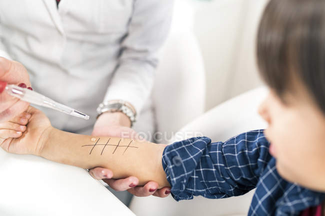Female doctor performing allergy skin prick test on little boy arm. — Stock Photo