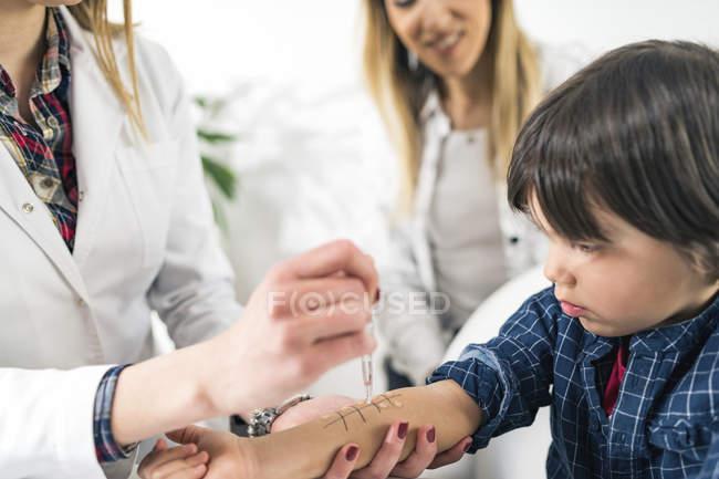 Kinderärztin führt Allergie-Hautstichtest bei kleinem Jungen mit Mutter in Immunologie-Praxis durch. — Stockfoto