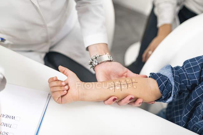 Manos del inmunólogo realizando pruebas de alergia al pinchazo cutáneo en un niño . - foto de stock