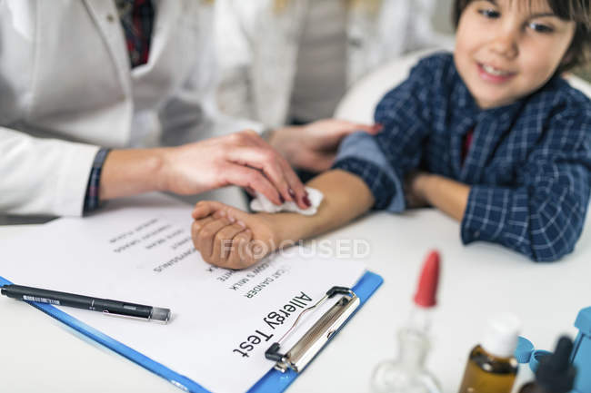 Female immunologist wiping boy arm after skin prick allergy testing. — Stock Photo