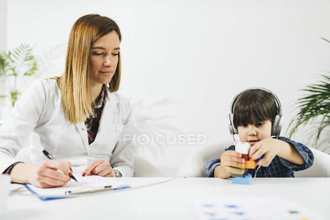 Junge trägt Kopfhörer als Spiel mit Bausteinen beim Hörtest mit Frau, die Notizen macht. — Stockfoto