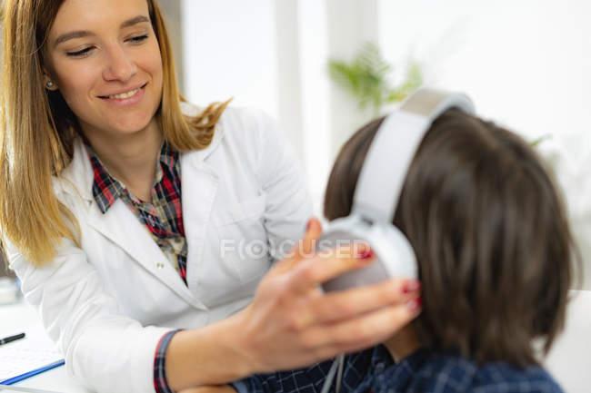 Ärztin setzt Jungen beim Hörtest Kopfhörer auf. — Stockfoto