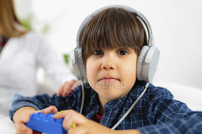 Niño usando auriculares como tener prueba de audición, médico femenino poniendo la mano en el hombro del niño . - foto de stock