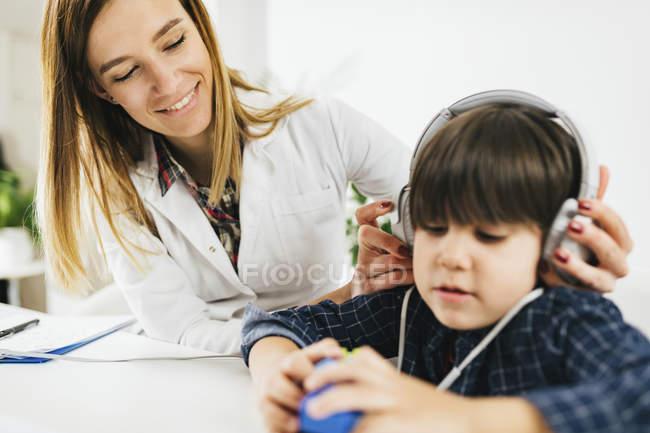 Chico teniendo una prueba de audición en el consultorio de un audiólogo . - foto de stock