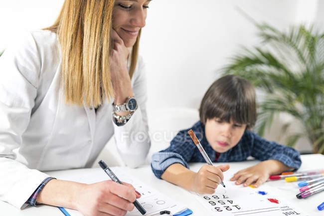 Niño en edad preescolar sometido a prueba lógica con números para prueba de psicología del desarrollo en consultorio de psicóloga femenina . - foto de stock