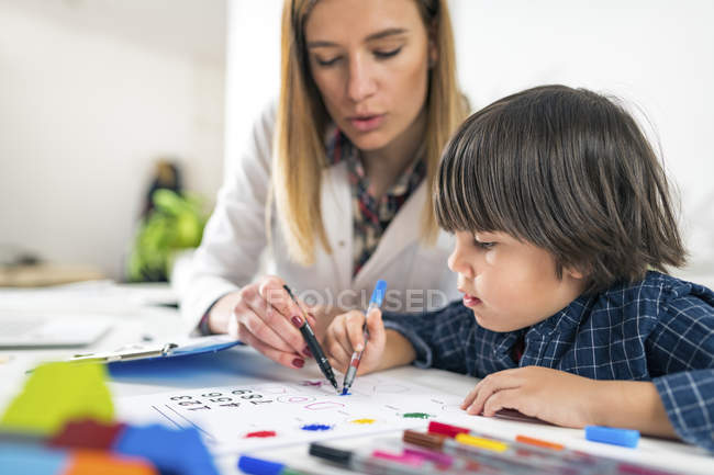 Female psychologist  helping boy coloring shapes with colorful pens for developmental psychology test. — Stockfoto
