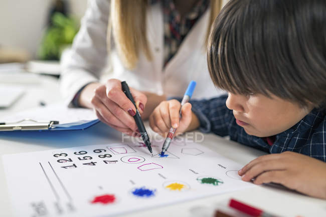 Preschooler boy coloring shapes with colorful pens for developmental psychology test in psychologist office. — Stock Photo