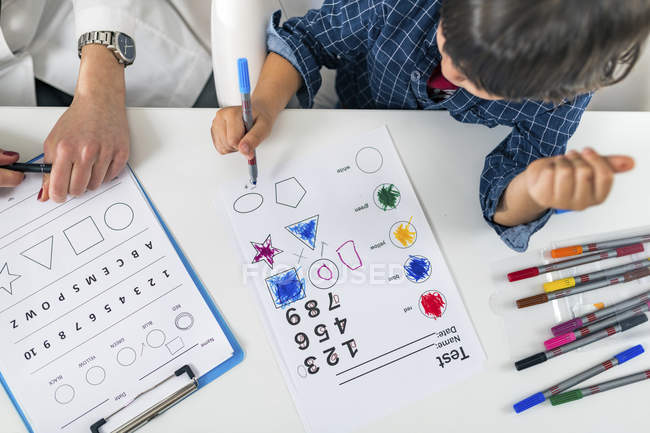 Preschooler boy coloring shapes with colorful pens for developmental psychology test in psychologist office. — Stockfoto