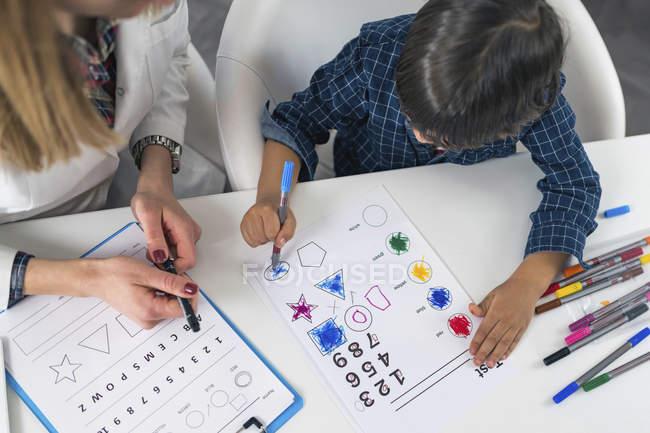 Pequeño niño para colorear formas con plumas de colores para la prueba de psicología del desarrollo en la oficina del psicólogo . - foto de stock