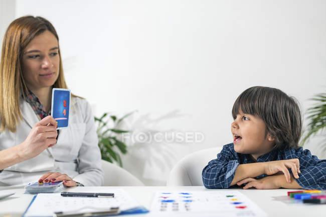 Niño en edad preescolar sometido a prueba de tarjetas lógicas para la prueba de psicología del desarrollo en la oficina de psicóloga femenina . - foto de stock