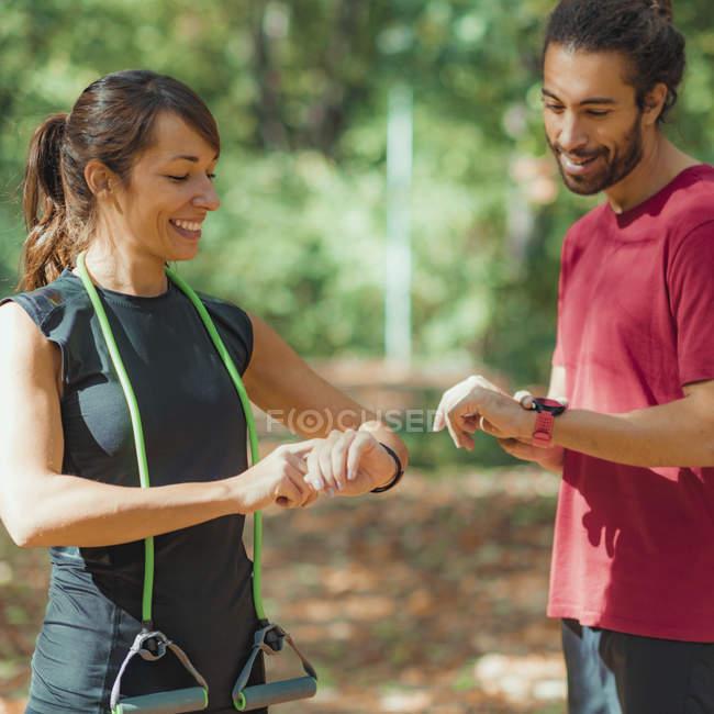Dos jóvenes que comprueban el progreso de los chanchullos después de la formación al aire libre. - foto de stock