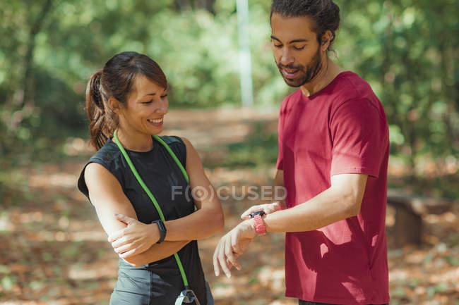 Hombre joven que comprueba el progreso en el smartwatch después de una formación al aire libre con una amiga.. - foto de stock