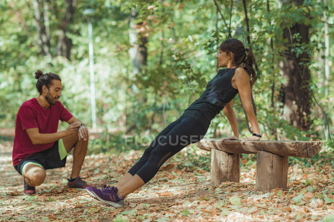 Woman doing push-ups in park with personal trainer. — Stock Photo