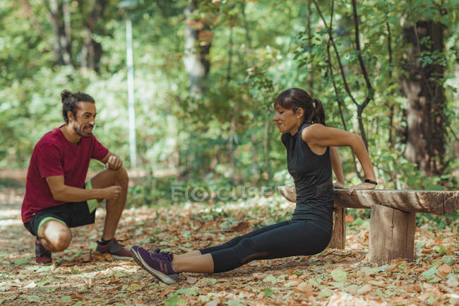 Young woman doing push-ups in park with personal trainer. — Stock Photo