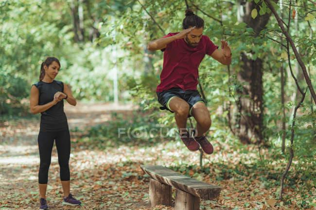 Jeune homme sautant par-dessus banc en bois tout en s'entraînant avec entraîneur personnel dans le parc . — Photo de stock