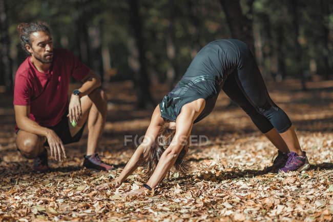 Женщина в позе собачьей йоги с лицом вниз во время тренировки с личным тренером в парке . — стоковое фото