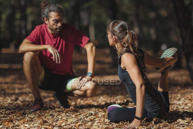 Jovem mulher esticando as pernas após o treinamento com personal trainer no parque . — Fotografia de Stock