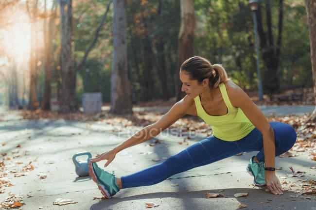 Женщина растягивает ноги во время занятий спортом на открытом воздухе в осеннем парке . — стоковое фото