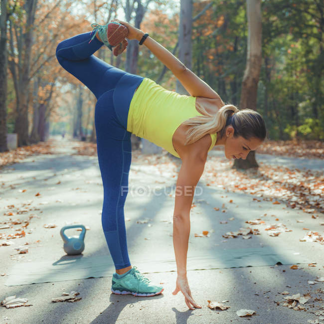 Woman stretching and bending while exercising in autumn park. — Stock Photo