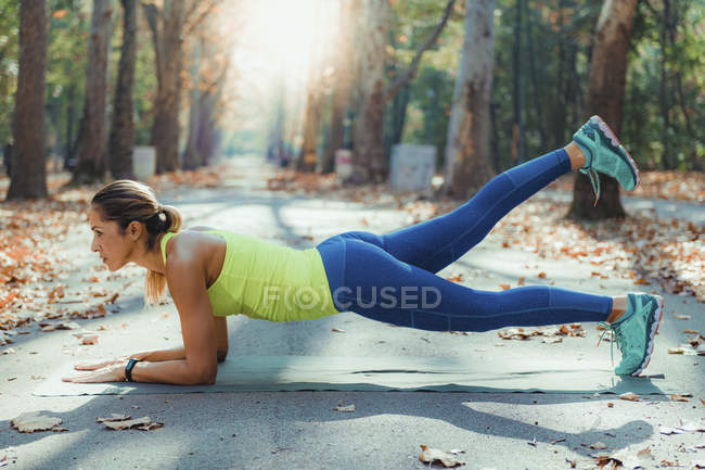 Woman exercising while lifting legs in plank outdoors in autumn park. — Stock Photo