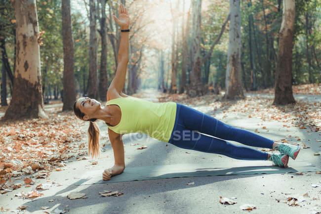 Жінки роблять побічну дошку під час фізичних вправ на відкритому повітрі в осінньому парку.. — стокове фото