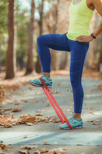 Обрезанный женщина делает ноги упражнения с сопротивлением полосы на открытом воздухе в осеннем парке . — стоковое фото