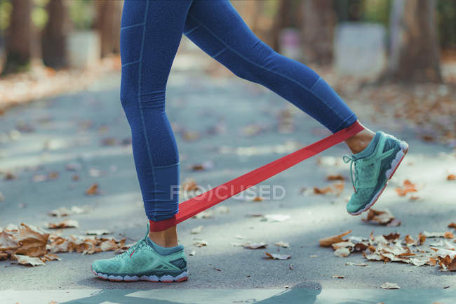 Низкая часть женщин, занимающихся спортом с полосой сопротивления в парке . — стоковое фото