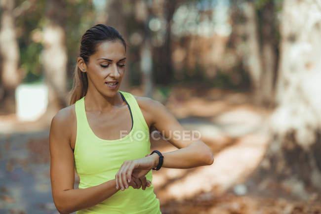 Mujer que comprueba los progresos realizados en el aserradero después de la formación al aire libre en el parque de otoño. - foto de stock