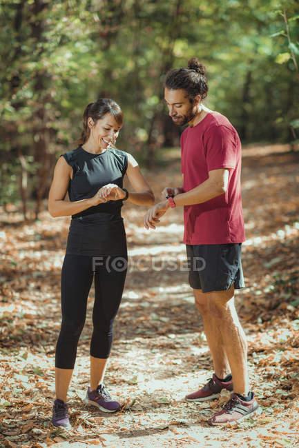 Jovens casais verificando o progresso em smartwatches enquanto treinam ao ar livre . — Fotografia de Stock