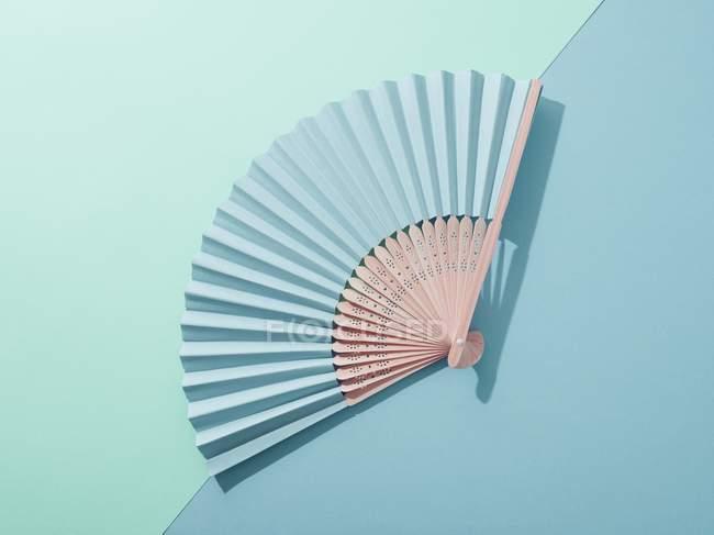 Ручной вентилятор на двухтонном синем фоне — стоковое фото