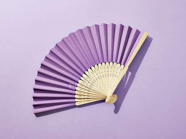 Бумажный вентилятор на фиолетовом фоне . — стоковое фото