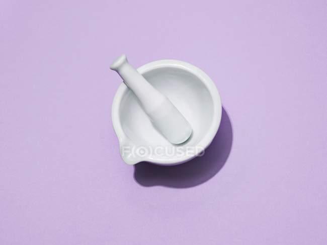 Пестл і міномет на фіолетовому фоні, знімок студії. — стокове фото