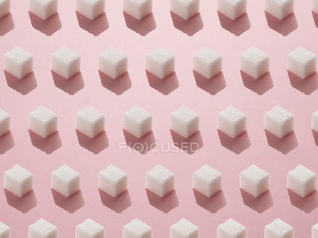 Modelo de cubos de azúcar en el fondo rosa. - foto de stock