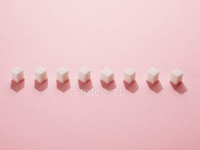 Row of sugar cubes on pink background. - foto de stock