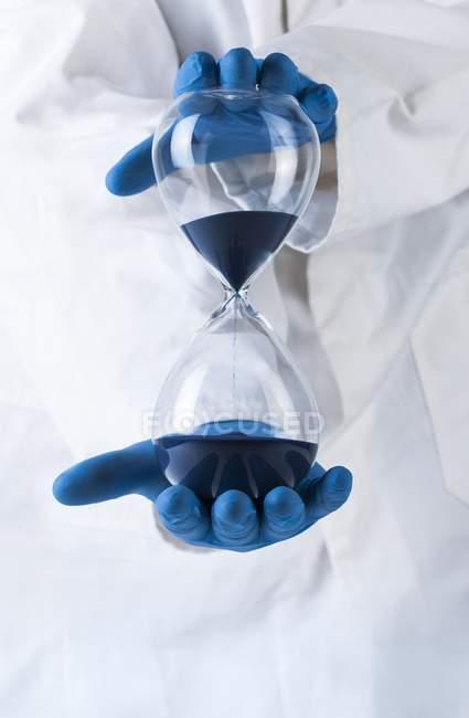 Reloj de arena en manos de científicos, imagen conceptual del paso del tiempo . - foto de stock