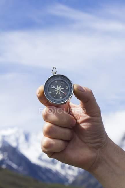 Mano de persona sosteniendo brújula magnética contra cielo azul y montañas . - foto de stock