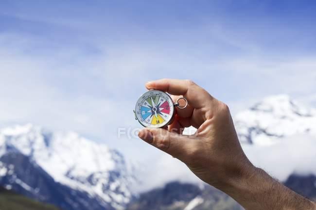 Рука человека держит магнитный компас на фоне голубого неба и гор . — стоковое фото