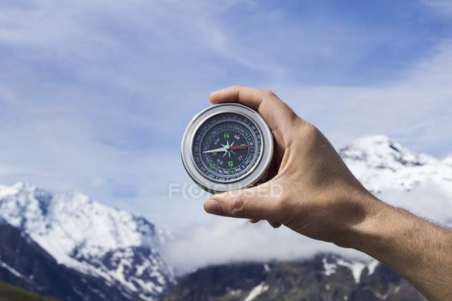 Person hand holding magnetic compass against blue sky and mountains. — Stock Photo
