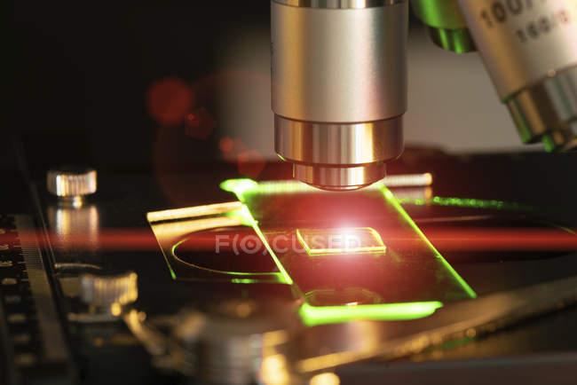 Lente per microscopio e diapositiva per luce laser, primo piano . — Foto stock