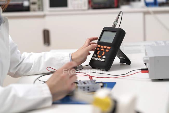 Ingegnere elettrico che lavora su circuiti stampati e pulsanti di pressione di dispositivi elettronici . — Foto stock