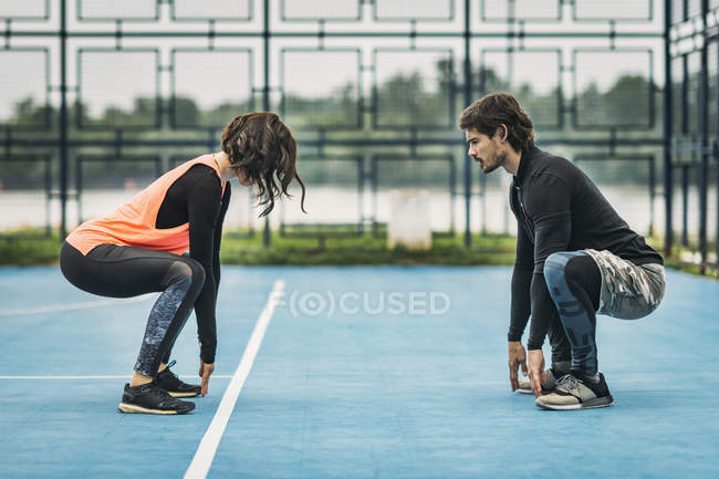 Young sporty woman crouching exercise outdoors with personal fitness trainer. — Stock Photo