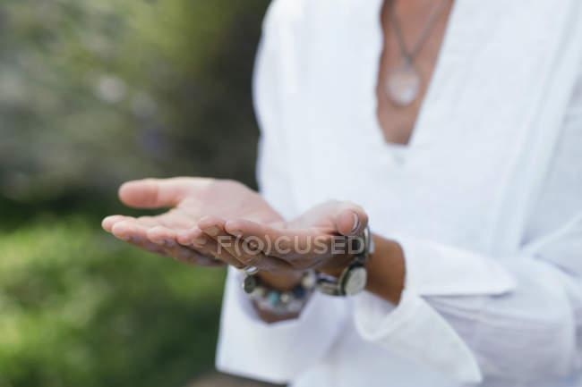Primo piano delle mani della donna che esercita la virtù del dare, del gesto della mano, delle palme sollevate verso l'alto. — Foto stock
