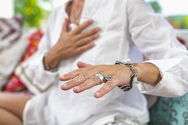 Donna seduta in posizione loto vestita di bianco esprimendo gratitudine con le mani. — Foto stock