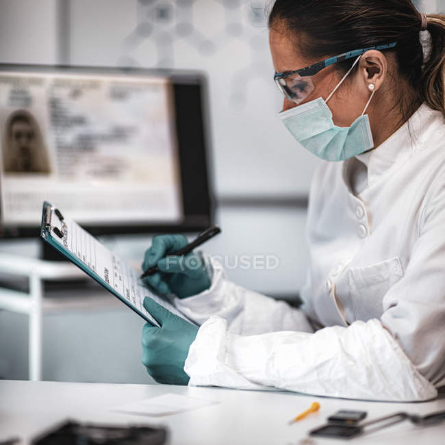 Female digital forensic science expert taking notes while investigation. — Stock Photo
