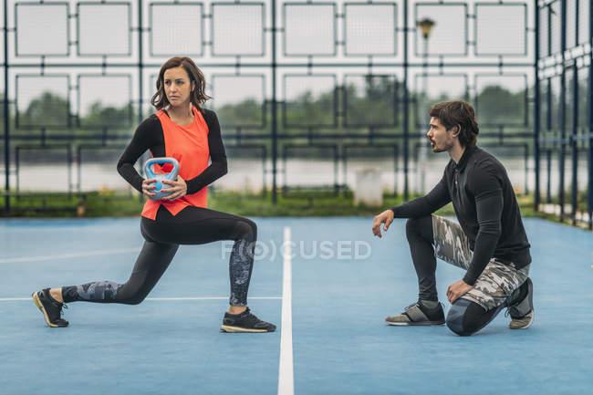 Treinador de fitness pessoal trabalhando com a jovem fazendo kettlebell exercício ao ar livre . — Fotografia de Stock