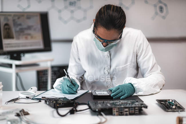 Female digital forensic expert examining computer hard drive and taking notes in police science laboratory. — Stock Photo